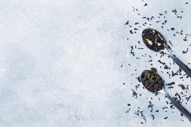 Variedade de folhas secas de chá e flores em colheres no fundo cinza copie o espaço