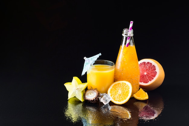 Variedade de frutas e sucos em fundo preto