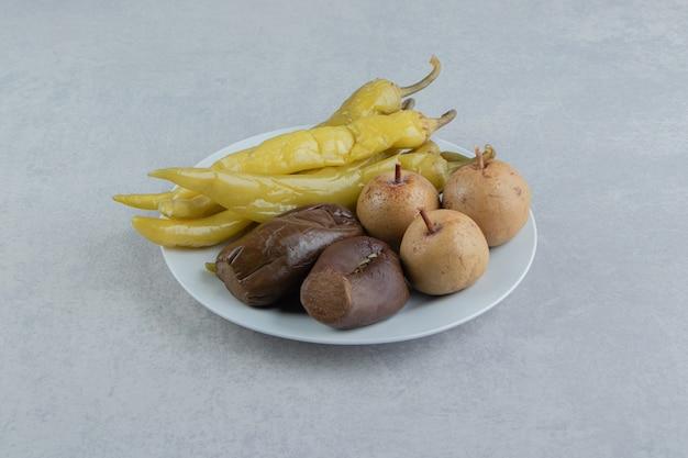 Variedade de frutas e vegetais fermentados em prato branco