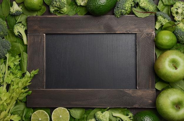 Variedade de frutas e vegetais verdes com placa de ardósia