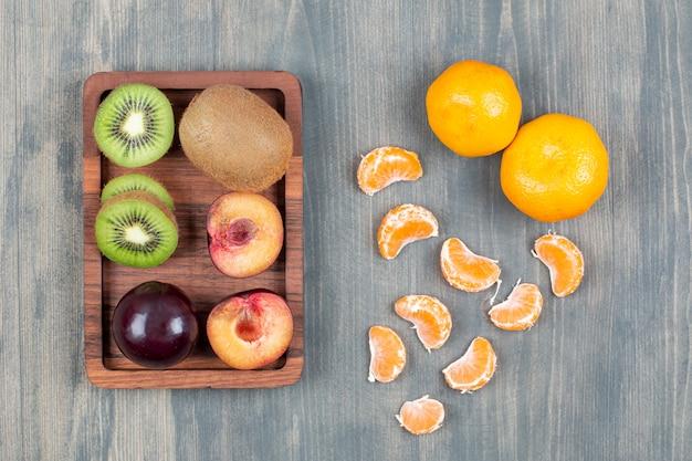 Variedade de frutas frescas em prato de madeira