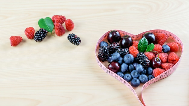 Variedade de frutas frescas maduras na mesa de madeira, dosando a fita como um símbolo de alimentação saudável e dieta de frutas.