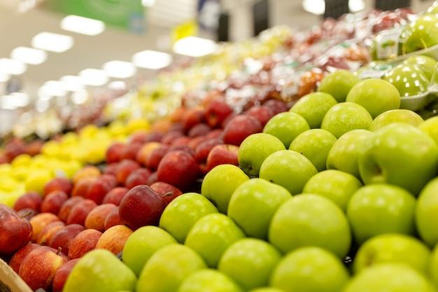 Variedade de frutas frescas no mercado, fundo desfocado e luzes.
