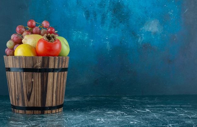 Variedade de frutas saborosas em balde de madeira.
