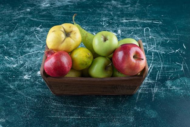 Variedade de frutas saborosas em caixa de madeira.