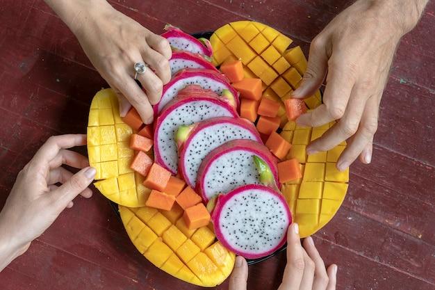 Variedade de frutas tropicais e mãos de pessoas, close-up. sobremesa deliciosa. grupo de amigos felizes, tendo uma boa comida, curtindo a festa e a comunicação. manga, mamão, pitaiaiás e mãos, vista de cima