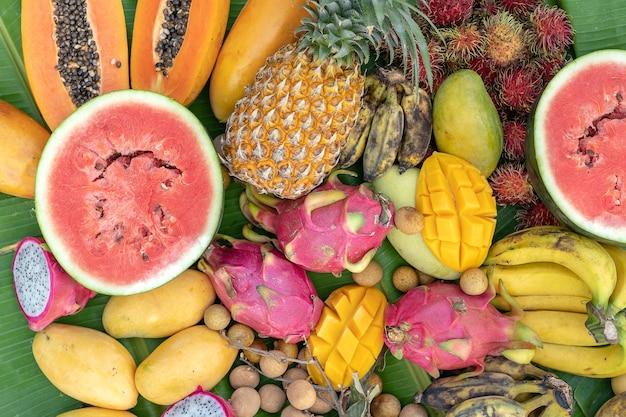 Variedade de frutas tropicais em folhas verdes de bananeira. sobremesa gostosa, close up. manga, mamão, banana, pitaiaia e melancia, vista de cima