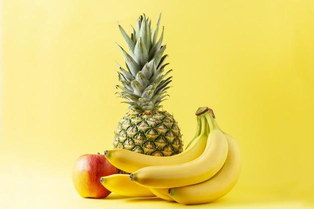 Variedade de frutas tropicais em fundo amarelo. abacaxi, banana e maçã.