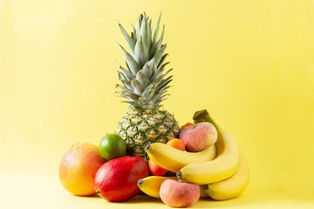 Variedade de frutas tropicais em fundo amarelo. abacaxi, banana, toranja, manga, damasco, limão e pêssegos