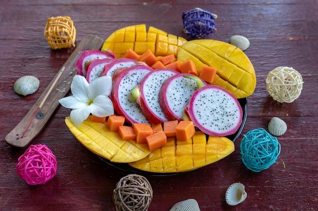Variedade de frutas tropicais em um prato, close-up. muitos fundo colorido de frutas tropicais maduras. manga, mamão e pitaiaia