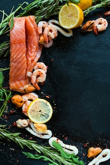Variedade de frutos do mar e salmão em superfície escura. gorduras insaturadas de ácido ômega 3. alimentação saudável. conceito de cozinha mediterrânea
