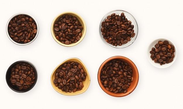 Variedade de grãos de café em várias tigelas, isoladas no fundo branco. sementes torradas, vista de cima, espaço de cópia