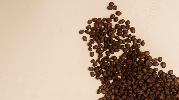 Variedade de grãos de café preto sobre fundo bege, com espaço de cópia
