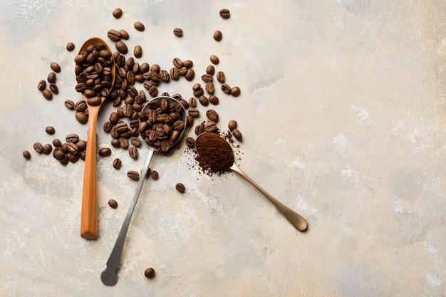 Variedade de grãos de café preto sobre fundo claro, com espaço de cópia