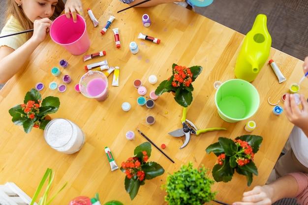 Variedade de guache. vista superior dos alunos usando guache colorido enquanto colorem baldes para plantas na aula de ecologia