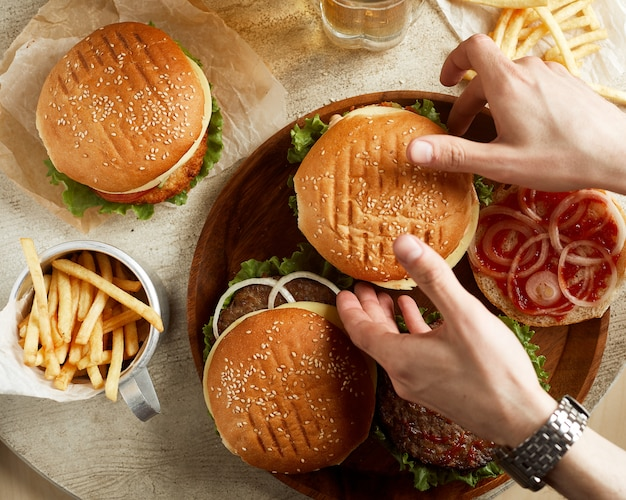 Variedade de hambúrgueres com batata frita e copo de cerveja