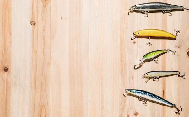 Variedade de isca de pesca colorida na mesa de madeira