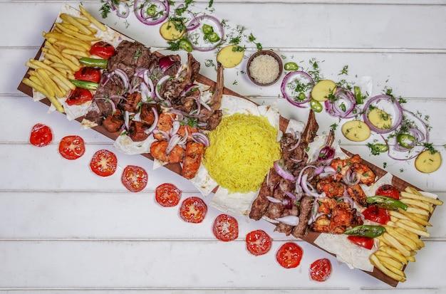 Variedade de kebab de carne com legumes grelhados e salada na mesa branca