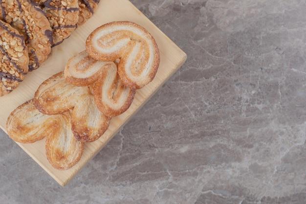 Variedade de lanches com biscoitos diferentes em uma pequena placa de mármore