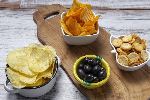 Variedade de lanches em casa com batata frita, cerveja, biscoitos, azeitonas verdes e pretas na mesa de madeira