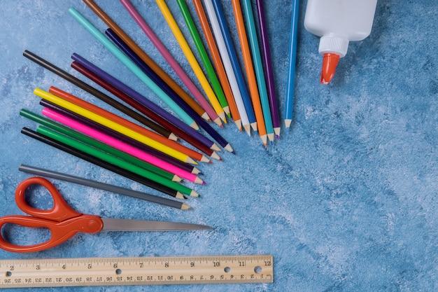Variedade de lápis de cor, régua, cola e tesoura