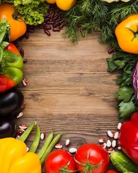 Variedade de legumes com vista superior e espaço de cópia em fundo de madeira
