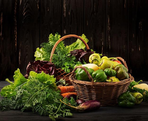 Variedade de legumes e ervas verdes. mercado. legumes em uma cesta em uma backgro escuro