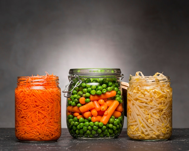 Variedade de legumes em conserva em potes de vidro