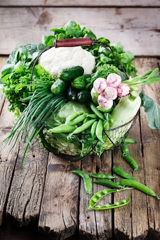 Variedade de legumes em uma cesta de arame em um fundo de madeira