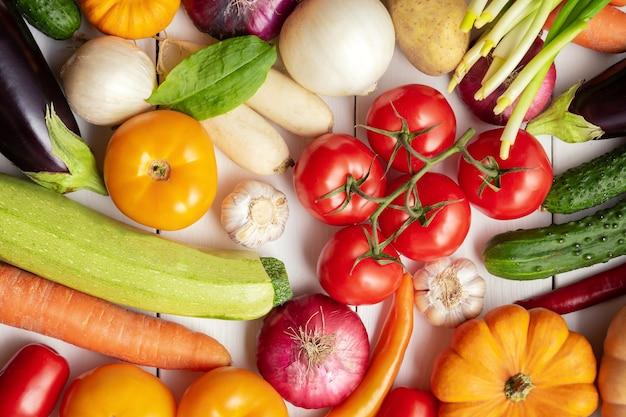 Variedade de legumes frescos como pano de fundo. sazonal perto da mesa do agricultor com legumes. abóboras, tomates, repolho, cenoura, cebola, pepino, melão, berinjela, batata e outros.