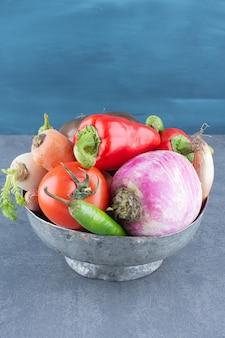 Variedade de legumes frescos em balde de ferro.