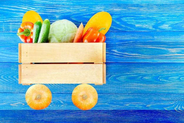 Variedade de legumes frescos em carro de madeira de brinquedo.