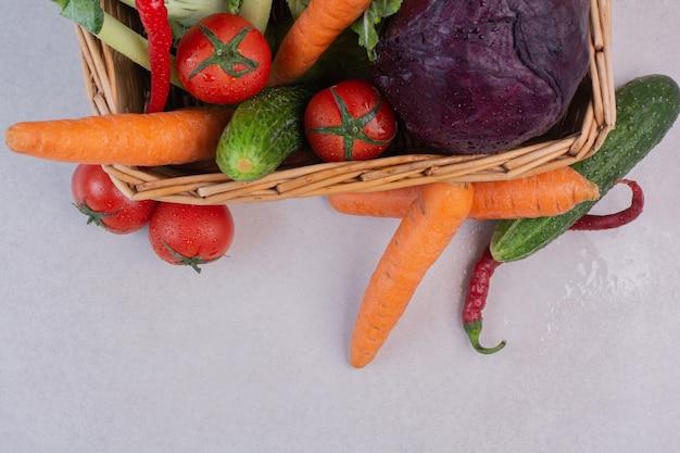 Variedade de legumes frescos em uma cesta de madeira.