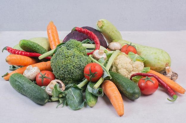 Variedade de legumes frescos na superfície branca.