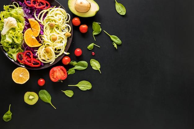 Variedade de legumes frescos picados e frutas em fundo preto