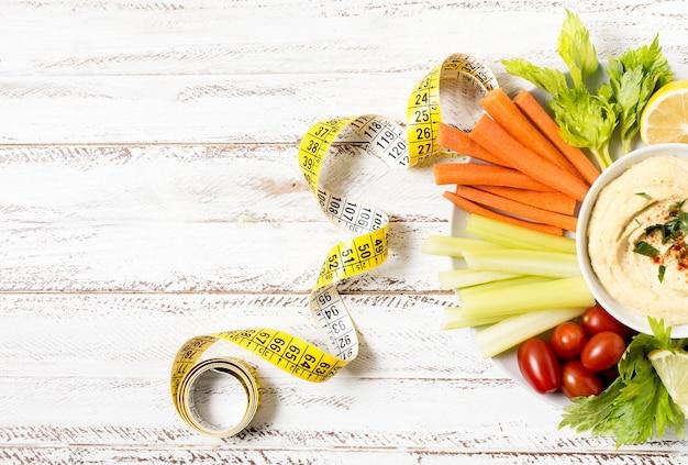 Variedade de legumes no prato com hummus e fita métrica