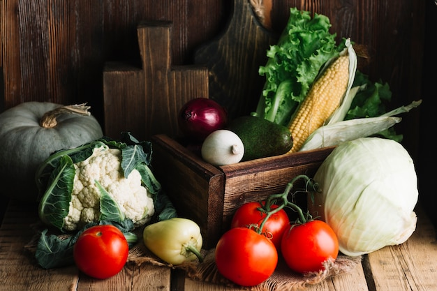 Variedade de legumes saborosos e tomates em fundo de madeira