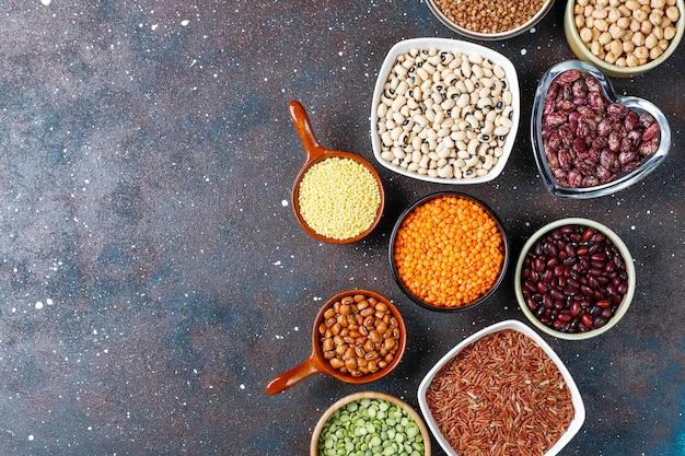 Variedade de leguminosas e feijões em tigelas diferentes sobre fundo claro de pedra. vista do topo. comida de proteína vegan saudável.