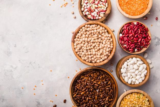 Variedade de lentilhas, grão de bico e feijão em diferentes tigelas na mesa de pedra branca.
