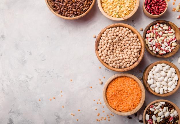 Variedade de lentilhas vermelhas, grão de bico e feijão em diferentes tigelas na mesa de pedra branca.