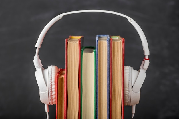 Variedade de livros com fones de ouvido