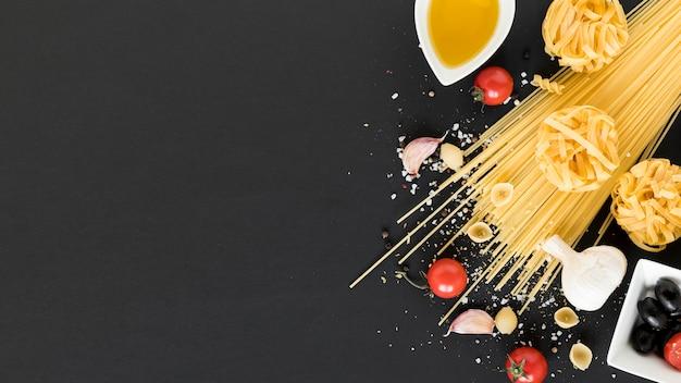Variedade de macarrão cru; tomate cereja; azeite; alho e azeitonas pretas sobre o pano de fundo preto