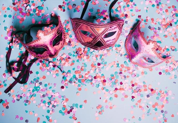 Variedade de máscara de olho de festa com confetes coloridos em pano de fundo azul