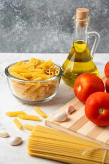 Variedade de massa crua, garrafa de azeite, grãos de pimenta e vegetais na mesa branca.