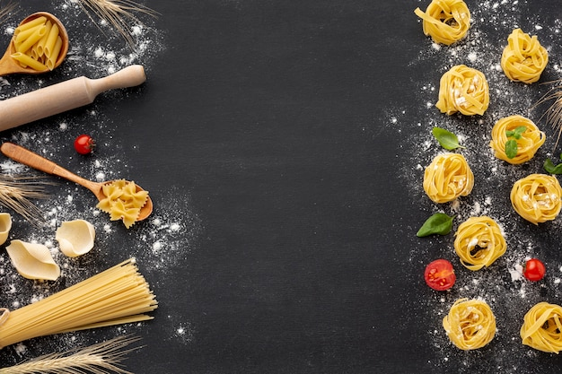 Variedade de massas alimentícias não cozidas com farinha no fundo preto