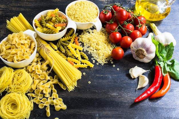 Variedade de massas italianas e ingredientes em fundo de madeira