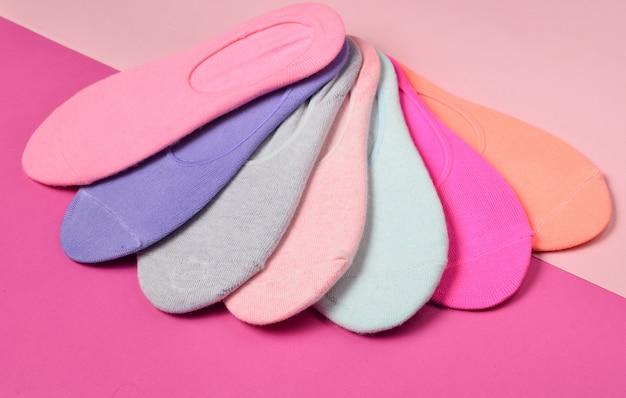 Variedade de meias coloridas em uma superfície colorida pastel. minimalismo, vista superior