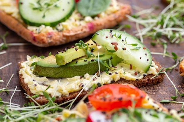 Variedade de mini sanduíches com cream cheese, verduras e salame. sanduíches com pepino, rabanete, tomate, salame em uma superfície cinza, vista superior. postura plana.