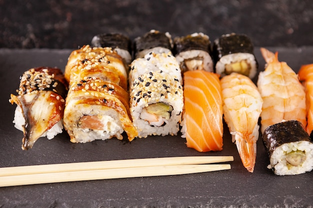 Variedade de mix de rolos de sushi em fundo preto em foto de estúdio