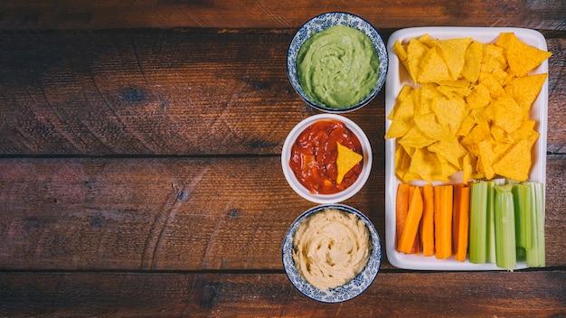 Variedade de molho em taças com chips nachos mexicanos; cenoura e aipo haste na bandeja sobre a mesa de madeira
